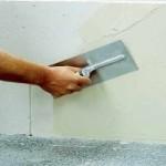 Процесс шпаклевания стен в помещении